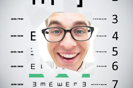 eye hole: Geeky hipster smiling through hole against eye test