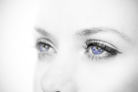 blue eyes: Close up of female blue eyes against earth