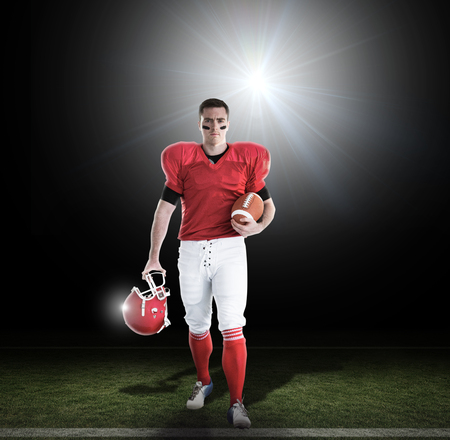 uniform green shoe: Portrait of american football player walking and holding football and helmet against lens flare