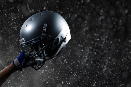cropped: Cropped hand of sportsman holding helmet against black background Stock Photo