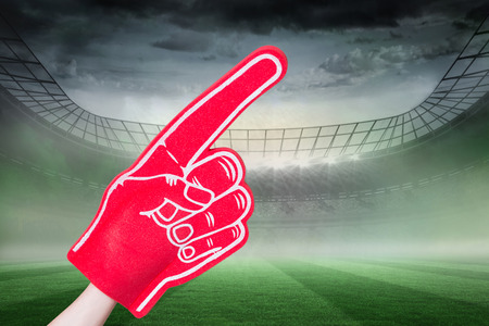foam hand: American football player holding supporter foam hand against rugby stadium