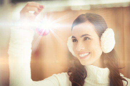 ear muffs: Pretty brunette with ear muffs holding bauble at home