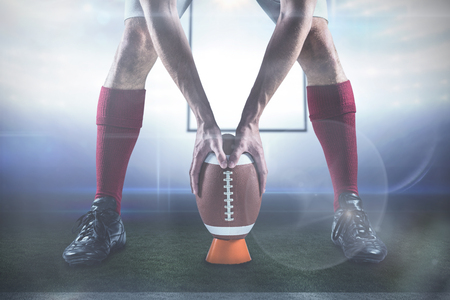 between: Low section of sports player placing the ball against american football arena Stock Photo