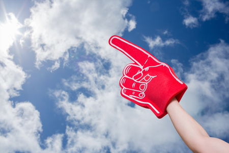 foam hand: American football player holding supporter foam hand against bright blue sky with clouds