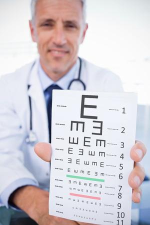 sense of sight: Portrait of a male doctor showing a blank prescription sheet against eye test