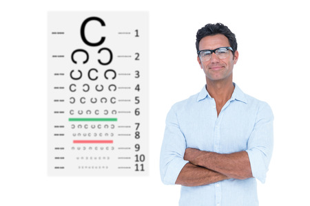 eye test: Confident man standing with arms crossed against eye test