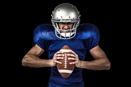 blue face: Portrait of aggressive American football player holding ball against black Stock Photo