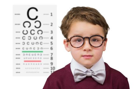 eye test: Cute schoolboy wearing reading glasses against eye test