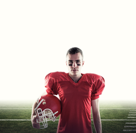 football pitch: A serious american football player looking at camera  against american football pitch