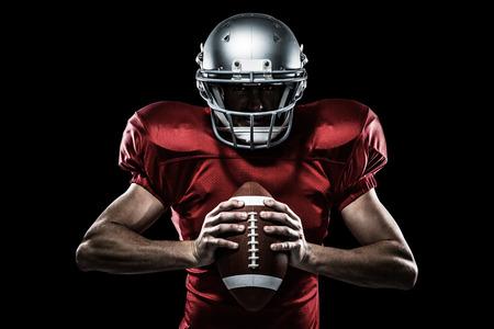 uniforme de futbol: El jugador de fútbol americano en camiseta roja y un casco que sostiene la bola contra el negro Foto de archivo