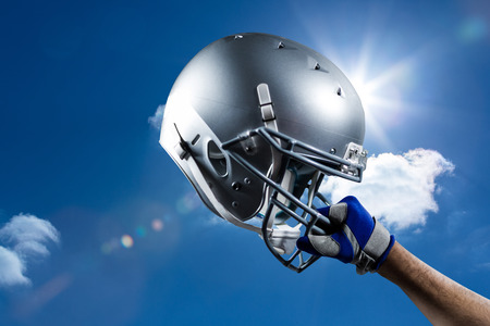 cropped: Cropped hand of sportsman holding helmet against sky