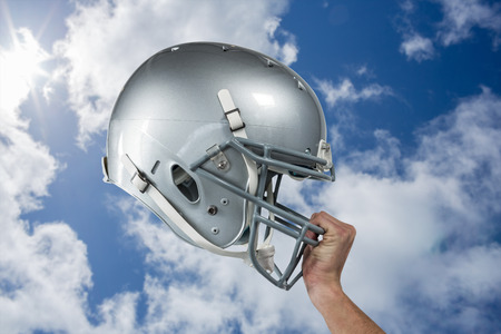 sliver: Close-up of American football player handing his sliver helmet against bright blue sky with clouds Stock Photo