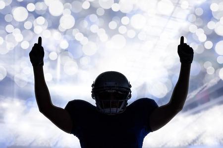 uniforme de futbol: Jugador de fútbol de la silueta americana con el pulgar hacia arriba contra el fondo brillante