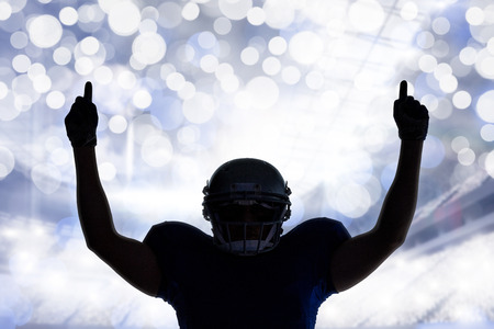 football fan: Silhouette American football player with thumbs up against glowing background