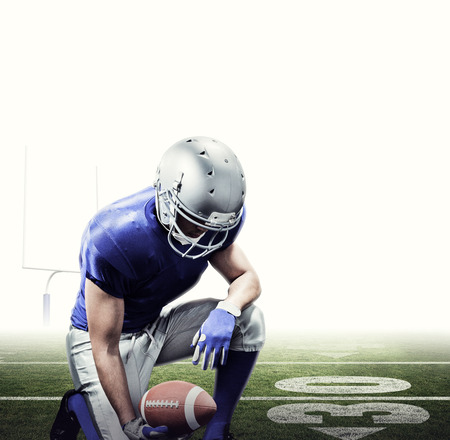 kneel down: American football player kneeling while holding ball against american football posts Stock Photo