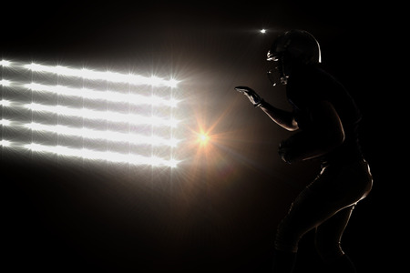 Silhouette sportsman playing American football against spotlights
