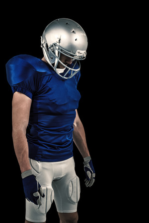 looking down: American football player looking down against black Stock Photo