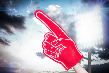 foam hand: American football player holding supporter foam hand against spotlight in sky