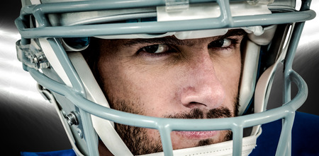 stern: Close-up portrait of stern American football player against spotlight Stock Photo