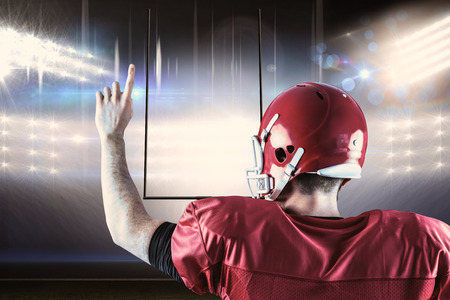 triumphing: Rear view of american football player triumphing  against american football arena