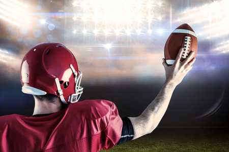 holding up: Rear view of american football player holding up football against sports pitch Stock Photo