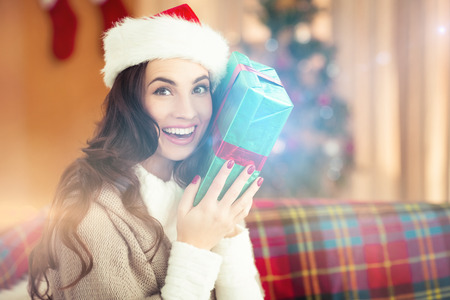 guessing: Festive brunette holding gift at christmas at home in the living room Stock Photo