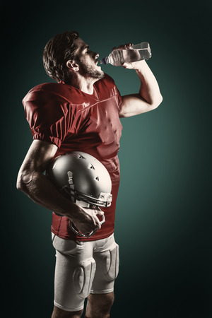 sediento: Jugador de f�tbol americano sed en el agua potable camiseta roja contra el fondo verde con la ilustraci�n