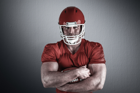 chrome man: American football player with ball against digitally generated grey vignette background