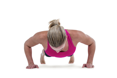 body concern: Portrait of pretty woman doing push ups against white background
