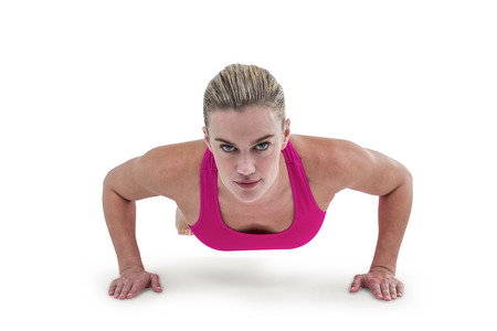 ups: Portrait of pretty woman doing push ups against white background