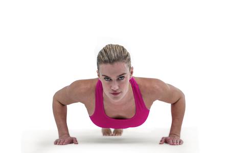 push ups: Portrait of pretty woman doing push ups against white background