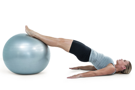 lean out: Muscular woman lying on floor with legs  on exercise ball
