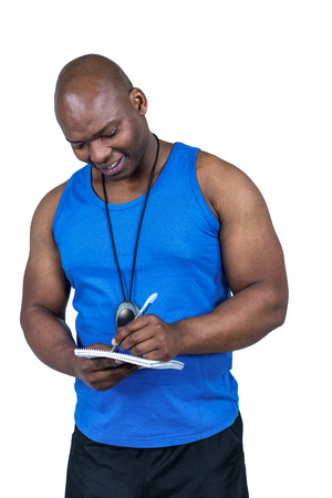 Fit trainer writing on notepad on white background Stock Photo