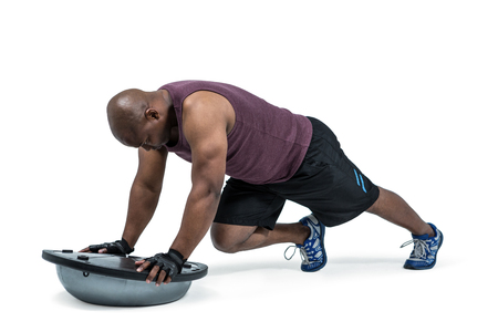 plank position: Fit man exercising with bosu ball on white background