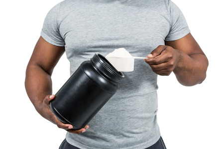 scooping: Fit man scooping protein powder on white background