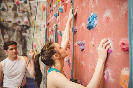 escalando: Instructor guiar la mujer en la pared de escalada en roca en el gimnasio
