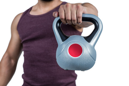 mid section: Mid section of a muscular man holding a kettlebell against white background