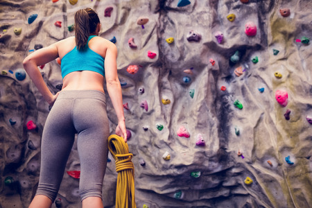 Fit woman looking up at rock climbing wall at the gym Standard-Bild