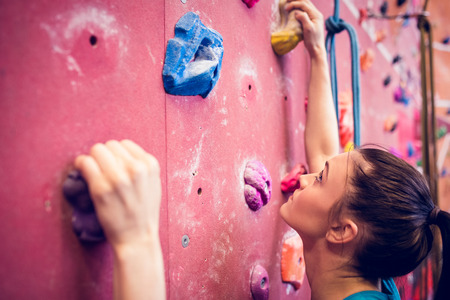 Fit woman rock climbing indoors  at the gym