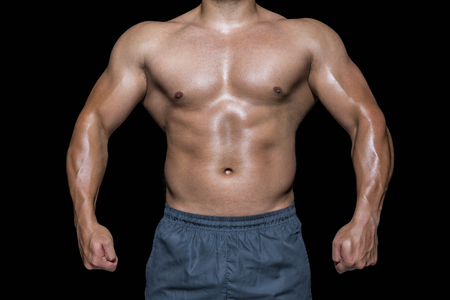 mid section: Mid section of a bodybuilder man against black background