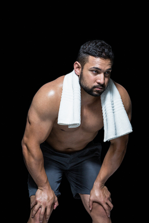 muslos: Bodybuilder man with hands on thighs against black background