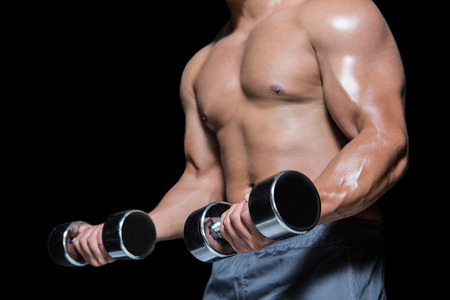 mid section: Mid section of a bodybuilder with dumbbells against black background Stock Photo