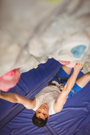 recreational climbing: Man climbing up rock wall at the gym