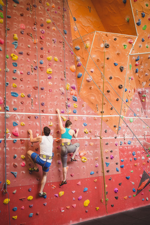 escalando: Pareja subiendo por la pared de roca en el gimnasio Foto de archivo