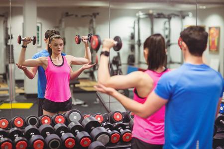 adentro y afuera: Pareja apta que se resuelve en la sala de pesas en el gimnasio