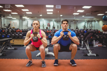 working out: Fit couple working out in weights room at the gym