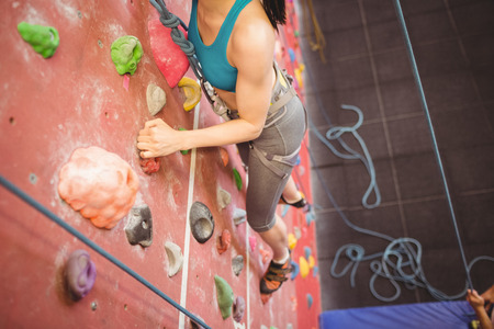 guiding: Instructor guiding woman on rock climbing wall at the gym Stock Photo