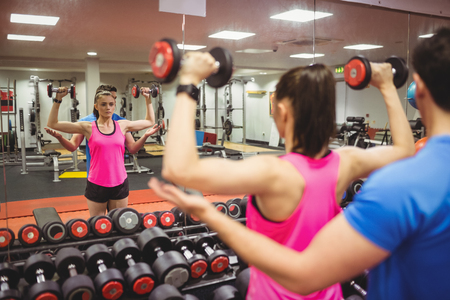 Fit couple working out in weights room at the gym