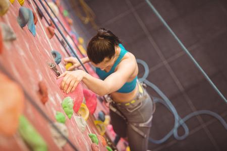 recreational climbing: Woman climbing up rock wall at the gym