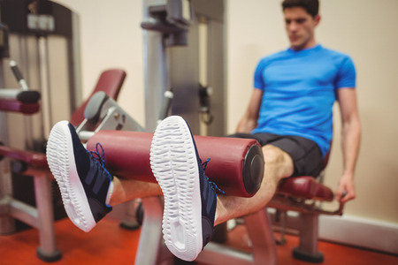man legs: Fit man using weights machine for legs at the gym